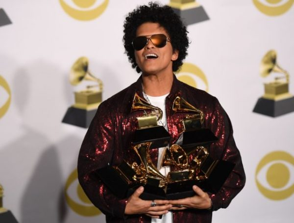 Singer Bruno Mars poses in the press room with his Grammy trophies during the 60th Annual Grammy Awards on January 28, 2018, in New York. / AFP PHOTO / Don EMMERT